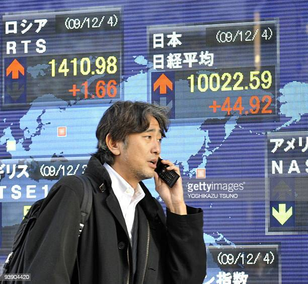 Pedestrians pass before a share prices board in Tokyo on December 4 2009 Japanese share prices rose 4492 points to close at 1002259 points at the...