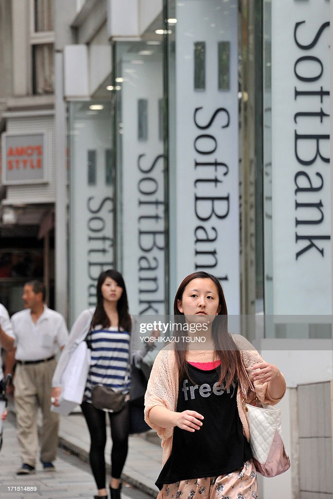 Pedestrians pass before a Softbank mobile phone shop in Tokyo on June 26, 2013. Sprint shareholders on June 25 overwhelmingly approved SoftBank's proposed 21.6 billion USD deal to take a controlling stake in the third largest US mobile carrier. AFP PHOTO / Yoshikazu TSUNO