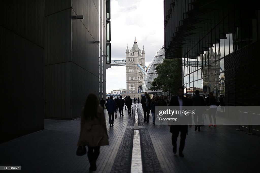 Pedestrians pass between buildings in the More London development as Tower Bridge stands beyond in London, U.K., on Wednesday, Sept. 18, 2013. U.K. commercial real estate values rose for the fourth straight month in August, led by office buildings and warehouses, Investment Property Databank Ltd. said. Photographer: Matthew Lloyd/Bloomberg via Getty Images
