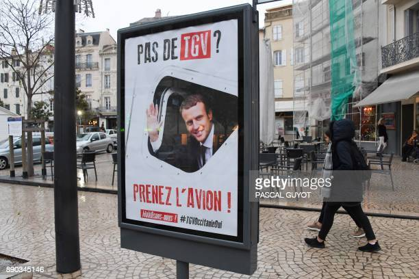 Pedestrians pass by a billboard with a poster launched at the request of Beziers' mayor as part of a campaign in favor of the TGV in the city showing...