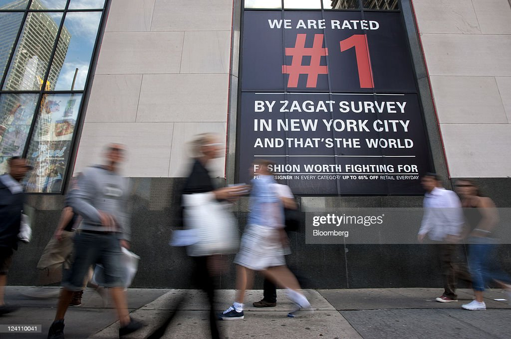 Pedestrians pass by a Centrury 21 store advertising its Zagat rating on a sign in New York, U.S., on Thursday, Sept. 8, 2011. Google Inc. acquired Zagat Survey LLC, the review and ratings service known for its burgundy-colored restaurant guides, bringing it features aimed at local businesses and advertisers. Photographer: Paul Taggart/Bloomberg via Getty Images