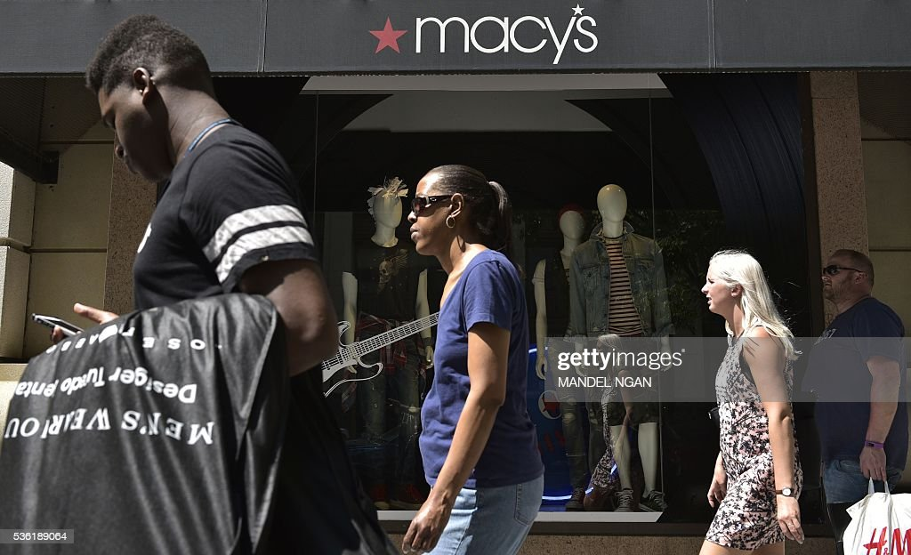 Pedestrians pass by a department store on May 31, 2016 in Washington, DC. US consumer confidence fell for the second straight month in May amid apparent caution over the economic situation, the Conference Board said May 31, 2016. / AFP / MANDEL