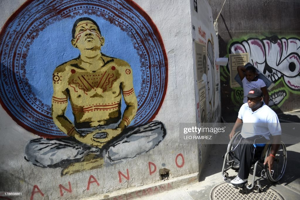 Pedestrians pass by a graffiti depicting late Venezuelan former President Hugo Chavez in Caracas on August 23, 2013. Nearly six month of his death, the image of Chavez still appears in buildings and corners of the country. AFP PHOTO/Leo RAMIREZ