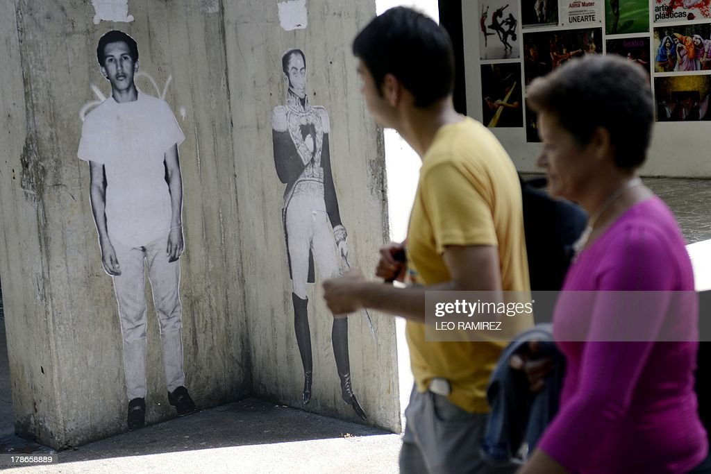 Pedestrians pass by a graffiti depicting late Venezuelan former President Hugo Chavez (L) besides XIX hero Simon Bolivar, in Caracas on August 23, 2013. Nearly six month of his death, the image of Chavez still appears in buildings and corners of the country. AFP PHOTO/Leo RAMIREZ