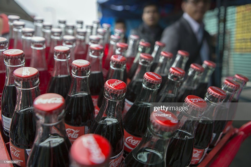 Pedestrians pass by a hand truck filled with Coca-Cola bottles in Mexico City, Mexico, on Thursday, Sept. 5, 2013. Coca-Cola Femsa SAB, a bottler and distributor of Coca-Cola products in Mexico, agreed to buy Brazils Spaipa SA Industria Brasileira de Bebidas in a cash deal with a total transaction value of $1.86 billion. Photographer: Susana Gonzalez/Bloomberg via Getty Images