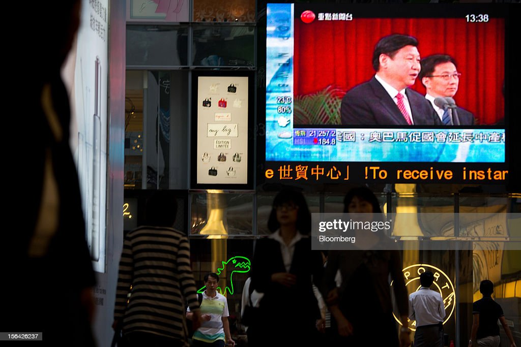 Pedestrians pass by a monitor showing a news broadcast of Xi Jinping, general secretary of the Communist Party of China, outside a mall in the shopping district of Causeway Bay in Hong Kong, China, on Thursday, Nov. 15, 2012. Xi Jinping replaced Hu Jintao as head of the Chinese Communist Party and the nation's military, ushering in the fifth generation of leaders who are set to run the world's second-biggest economy over the next decade. Photographer: Lam Yik Fei/Bloomberg via Getty Images