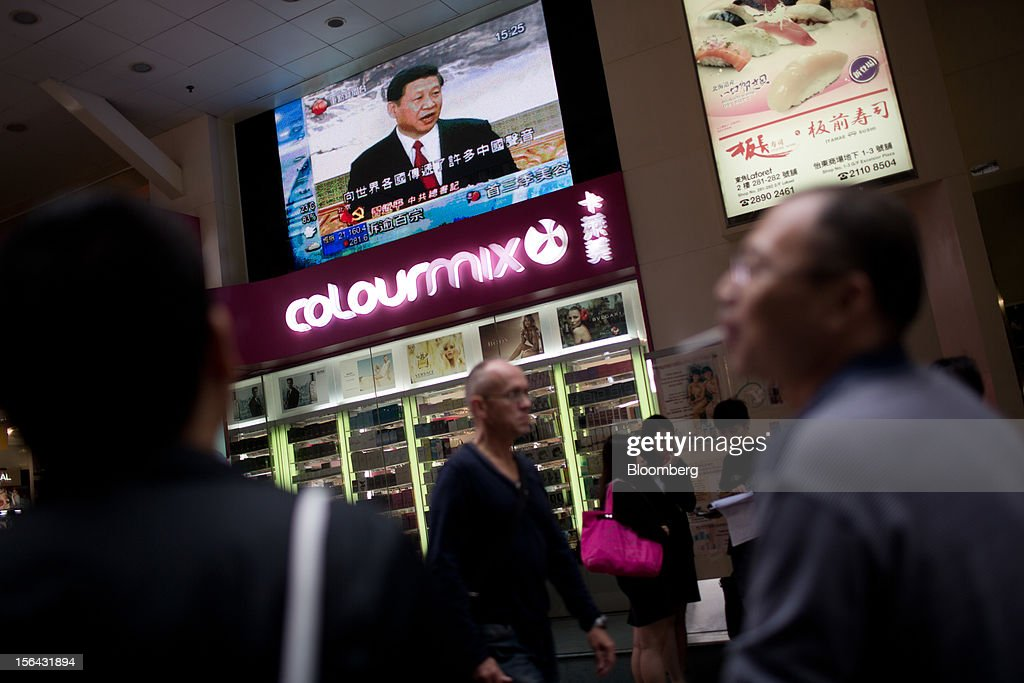 Pedestrians pass by a monitor showing a news broadcast of Xi Jinping, general secretary of the Communist Party of China, during a news conference introducing the new Politburo Standing Committee, outside a mall in the shopping district of Causeway Bay in Hong Kong, China, on Thursday, Nov. 15, 2012. Xi Jinping replaced Hu Jintao as head of the Chinese Communist Party and the nation's military, ushering in the fifth generation of leaders who are set to run the world's second-biggest economy over the next decade. Photographer: Lam Yik Fei/Bloomberg via Getty Images