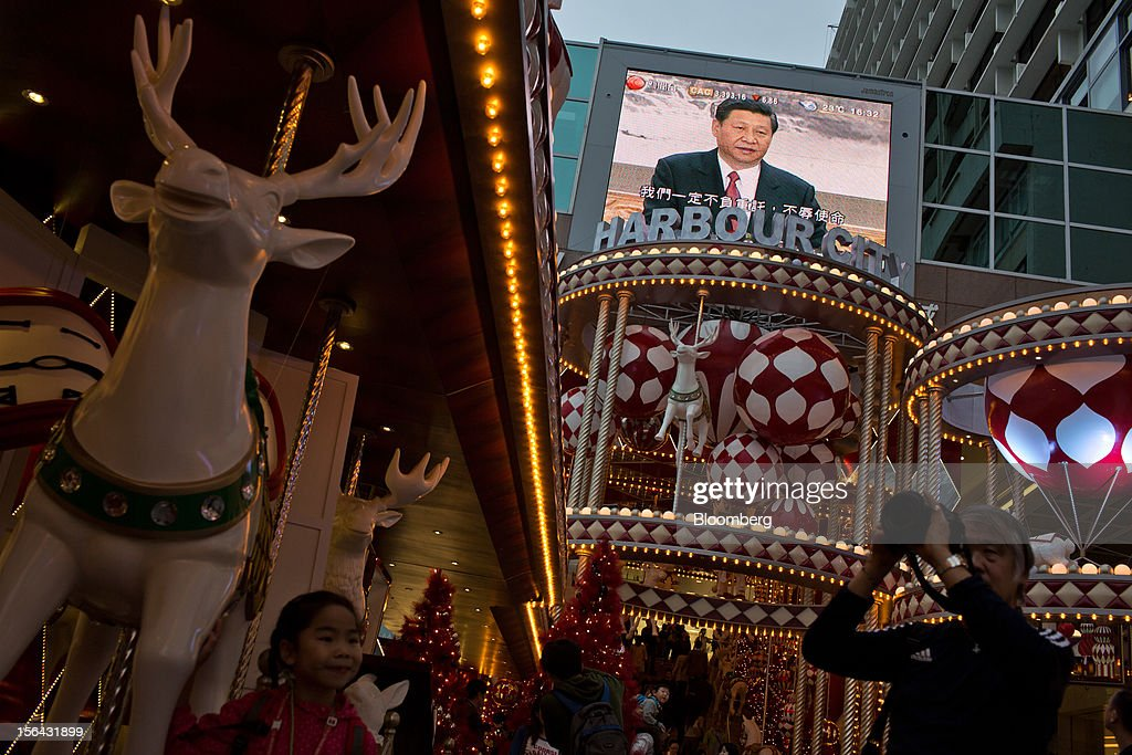 Pedestrians pass by a monitor showing a news broadcast of Xi Jinping, general secretary of the Communist Party of China, during a news conference introducing the new Politburo Standing Committee, outside a mall in the shopping district of Tsim Sha Tsui in Hong Kong, China, on Thursday, Nov. 15, 2012. Xi Jinping replaced Hu Jintao as head of the Chinese Communist Party and the nation's military, ushering in the fifth generation of leaders who are set to run the world's second-biggest economy over the next decade. Photographer: Lam Yik Fei/Bloomberg via Getty Images