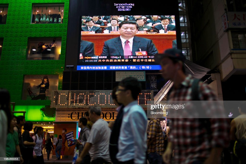 Pedestrians pass by a monitor showing a news broadcast of Xi Jinping, general secretary of the Communist Party of China, outside a store in the shopping district of Mong Kok in Hong Kong, China, on Thursday, Nov. 15, 2012. Xi Jinping replaced Hu Jintao as head of the Chinese Communist Party and the nation's military, ushering in the fifth generation of leaders who are set to run the world's second-biggest economy over the next decade. Photographer: Lam Yik Fei/Bloomberg via Getty Images
