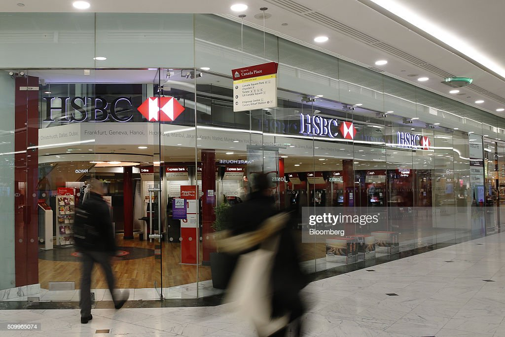 Pedestrians pass by the entrance to a HSBC Holdings Plc bank branch in the Canary Wharf business, financial and shopping district in London, U.K., on Saturday, Feb. 13, 2016. HSBC's board will meet on Sunday to decide whether to shift its headquarters from London, according to two people with knowledge of the decision. Photographer: Luke MacGregor/Bloomberg via Getty Images