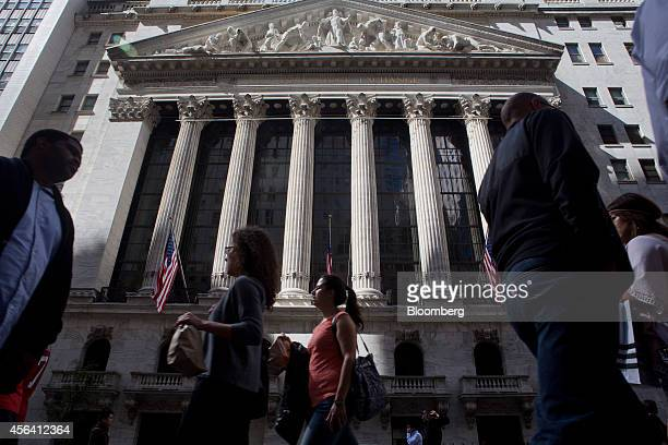 Pedestrians pass by the New York Stock Exchange in New York US on Friday Sept 26 2014 The SP 500 finished the quarter below its average price for the...