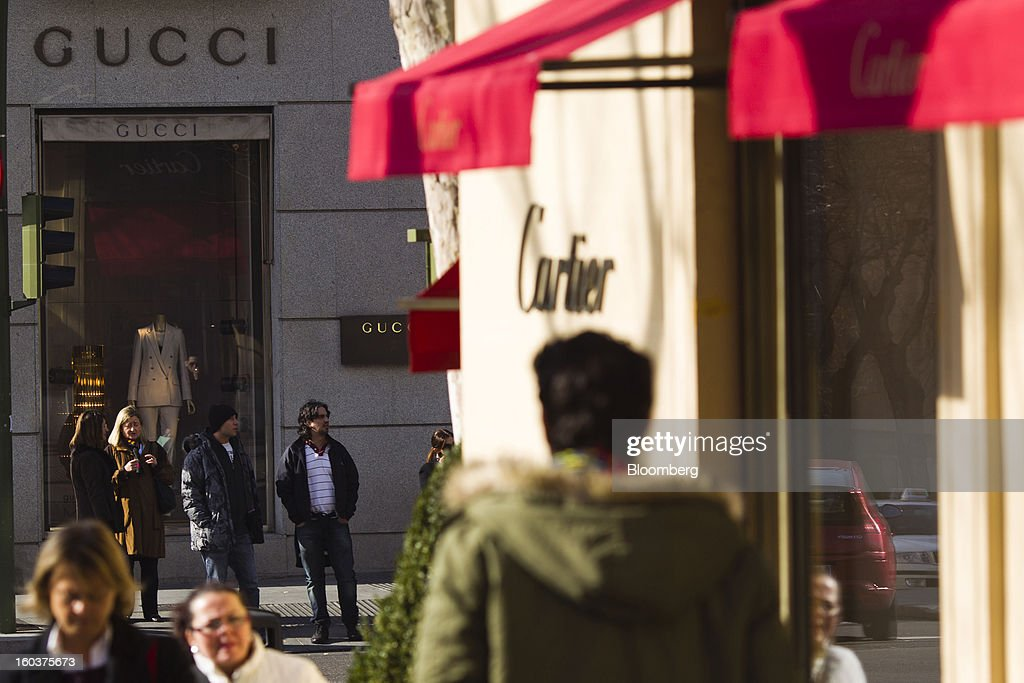 Pedestrians pass Cartier, operated by Cie. Financiere Richemont SA, and Gucci, a unit of PPR SA, luxury stores in Madrid, Spain, on Wednesday, Jan. 30, 2013. Spain's recession deepened more than economists forecast in the fourth quarter as the government's struggle to rein in the euro region's second-largest budget deficit weighed on domestic demand. Photographer: Angel Navarrete/Bloomberg via Getty Images