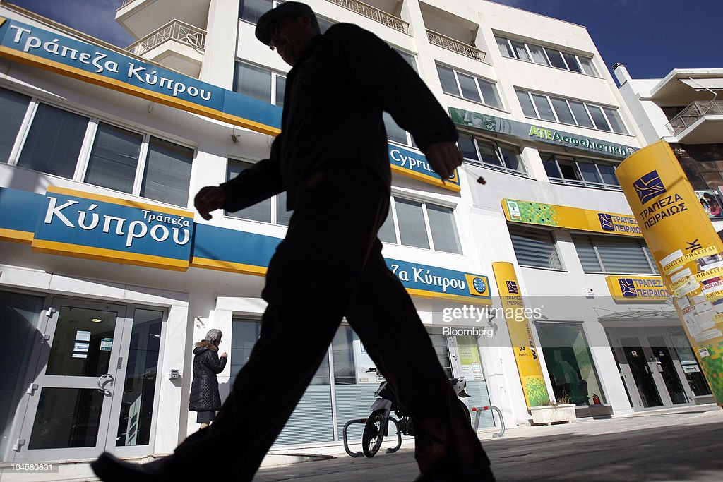 Pedestrians pass closed branches of Piraeus Bank SA, right, and Bank of Cyprus Plc, left, in Athens, Greece, on Tuesday, March 26, 2013. Piraeus Bank SA acquires Greek units of Cypriot lenders for total cash consideration of EU524m, according to e-mailed statement from the Athens-based lender today. Photographer: Kostas Tsironis/Bloomberg via Getty Images