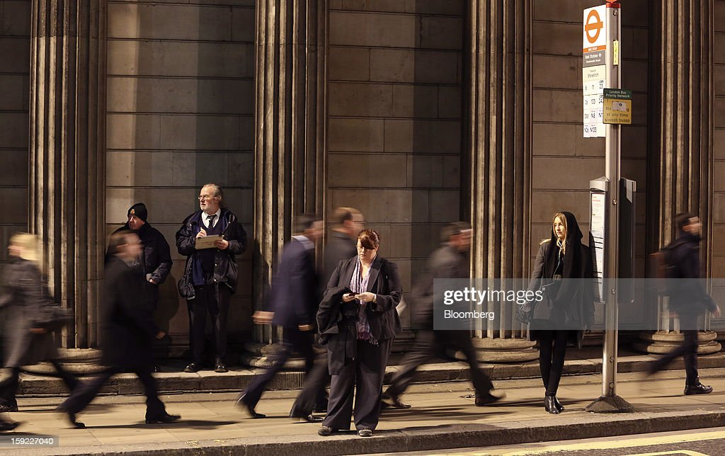Pedestrians pass commuters waiting at a bus stop outside the Bank of England (BOE) in London, U.K., on Wednesday, Jan. 9, 2013. Bank of England policy makers will probably refrain from adding further stimulus to the U.K. economy today as their new credit-boosting program shows early signs of success. Photographer: Chris Ratcliffe/Bloomberg via Getty Images