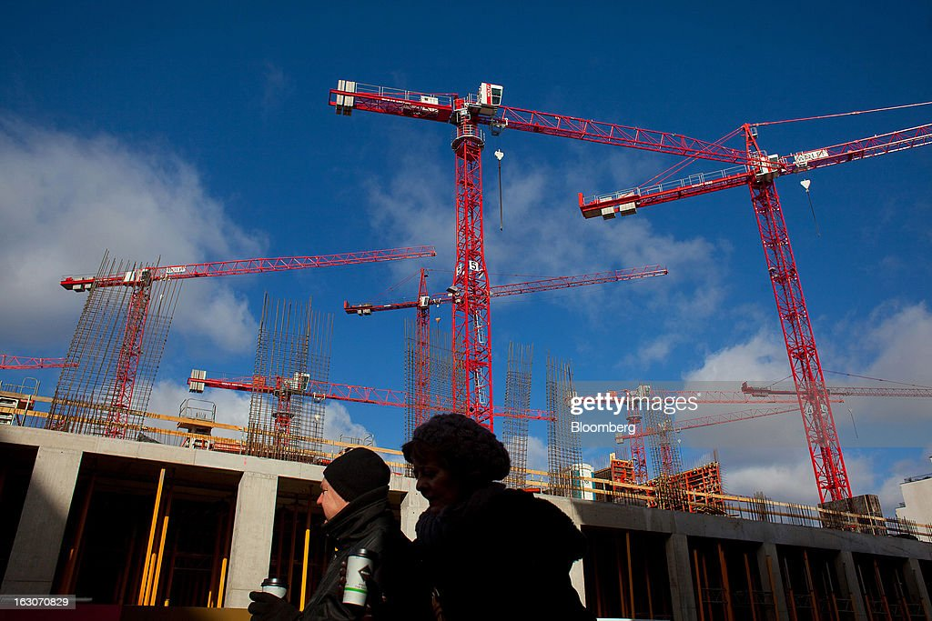 Pedestrians pass construction cranes in the Mitte district in Berlin, Germany, on Sunday, March 3, 2013. Germany's 10-year government bonds advanced for a second day even before a report that economists said will show producer prices in the euro area increased for the first time in four months in January. Photographer: Krisztian Bocsi/Bloomberg via Getty Images