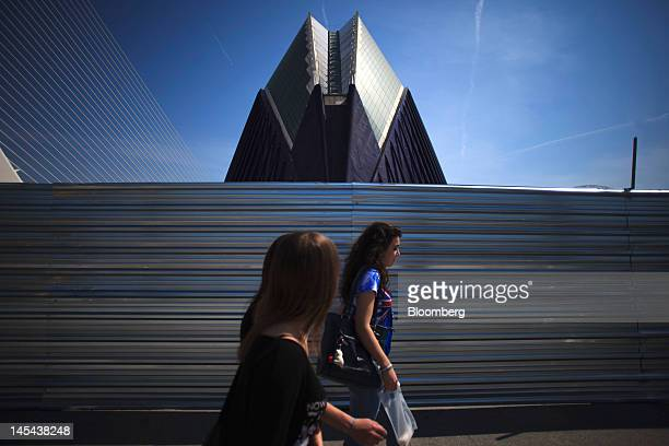 Pedestrians pass construction fencing outside the unfinished Agora center a multifunctional covered space designed by architect Santiago Calatrava at...