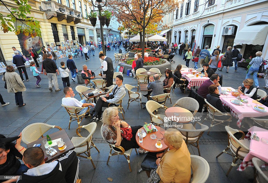 Pedestrians pass customers as they sit on the terrace of an outdoor cafe in Belgrade, Serbia, on Sunday, Oct. 20, 2013. Serbia's government revealed a salvo of measures to bring the public finance deficit and debt back under control by 2017 after the head of the largest coalition party warned the country was on the brink of insolvency. Photographer: Oliver Bunic/Bloomberg via Getty Images