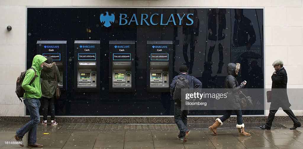 Pedestrians pass customers using automated teller machines (ATMs) at a Barclays Plc bank branch in London, U.K., on Monday, Feb. 11, 2013. Barclays Plc Chief Executive Officer Antony Jenkins's pledges to shred the legacy of his predecessor and fix the lender's culture are distracting from the difficulty he has in reviving profit at Britain's biggest investment bank. Photographer: Simon Dawson/Bloomberg via Getty Images