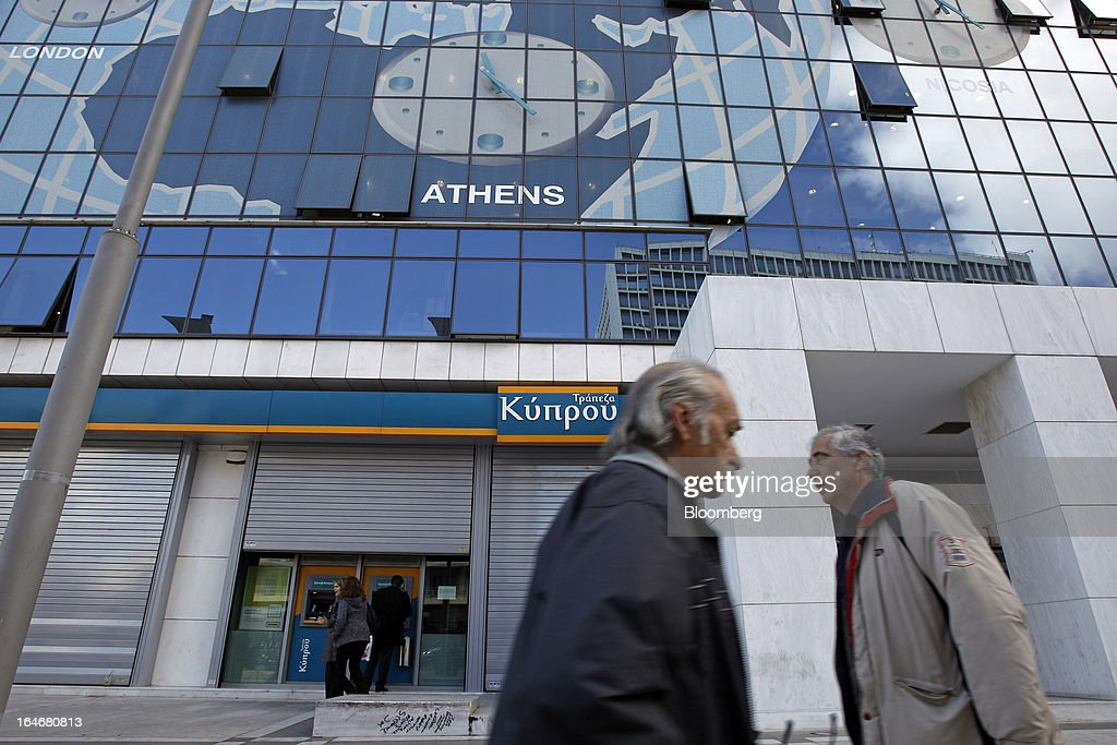 Pedestrians pass customers using automated teller machines (ATM) outside a closed Bank of Cyprus Plc branch in Athens, Greece, on Tuesday, March 26, 2013. Piraeus Bank SA acquires Greek units of Cypriot lenders for total cash consideration of EU524m, according to e-mailed statement from the Athens-based lender today. Photographer: Kostas Tsironis/Bloomberg via Getty Images