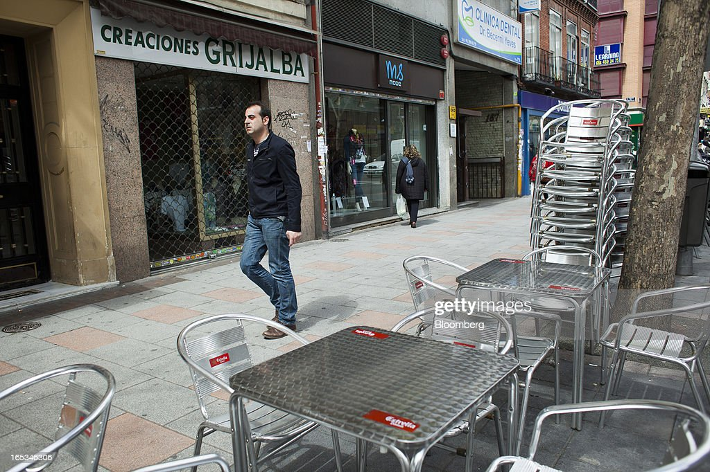Pedestrians pass empty cafe seating outside a closed-down store in Madrid, Spain, on Wednesday, April 3, 2013. Prime Minister Mariano Rajoy told Spaniards they'll start to see the benefits of his reform program next year after he avoided becoming the fifth European leader to request a full sovereign rescue. Photographer: Angel Navarrete/Bloomberg via Getty Images