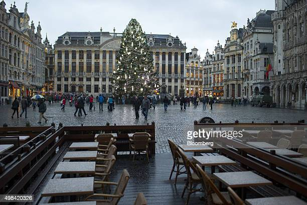 Pedestrians pass empty restaurant terrace seating in Grand Place square as a Christmas tree and an armored vehicle stand in Brussels Belgium on...