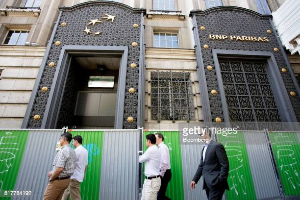 Pedestrians pass fencing for construction work outside the BNP Paribas SA headquarters in Paris France on Tuesday July 18 2017 BNP Paribas agreed to...
