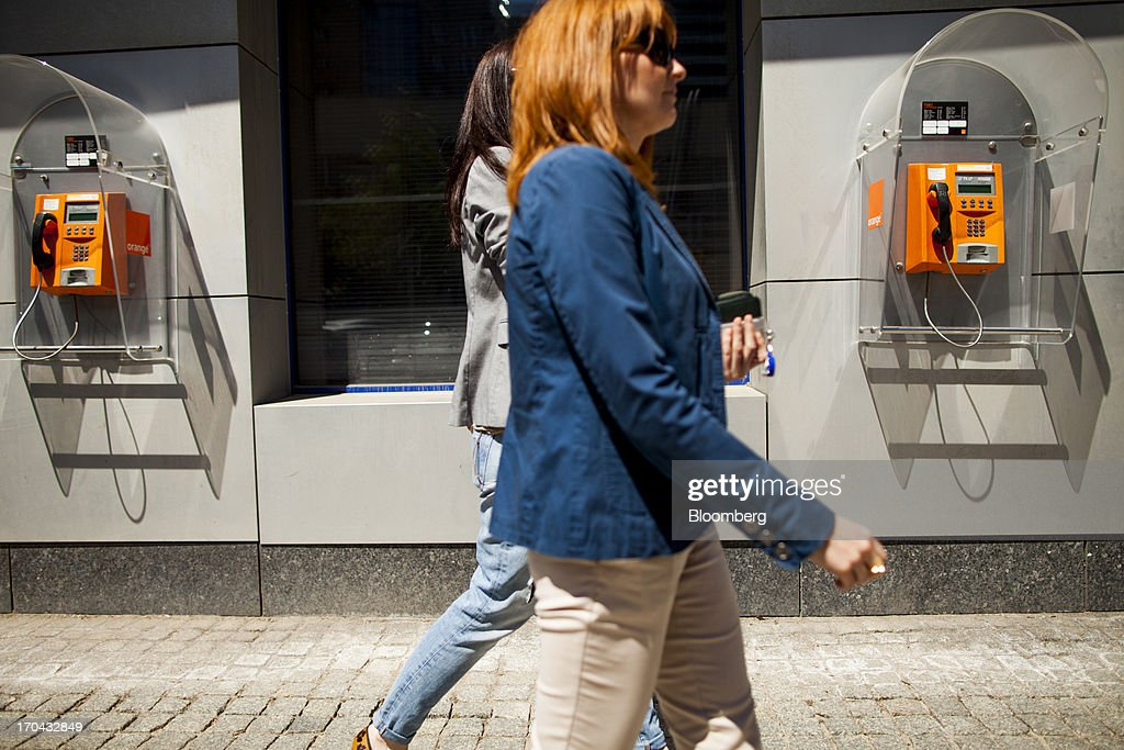 Pedestrians pass fixed line telephone booths outside the headquarters of Orange Polska, also known as Telekomunikacja Polska SA (TPSA), Poland's national telecommunications company, in Warsaw, Poland, on Wednesday, June 12, 2013. Cable providers are being drawn to Poland, the European Union's biggest eastern economy, because penetration levels are half that of neighboring Germany even as unemployment rises, according to a website presentation by the country's biggest TV network, Cyfrowy Polsat SA. Photographer: Bartek Sadowski/Bloomberg via Getty Images