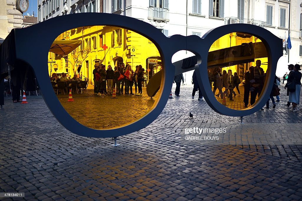 Pedestrians pass giant sunglasses in Piazza Farnese, d Rome as part of an advertising campaign on March 12, 2014. AFP PHOTO / GABRIEL BOUYS