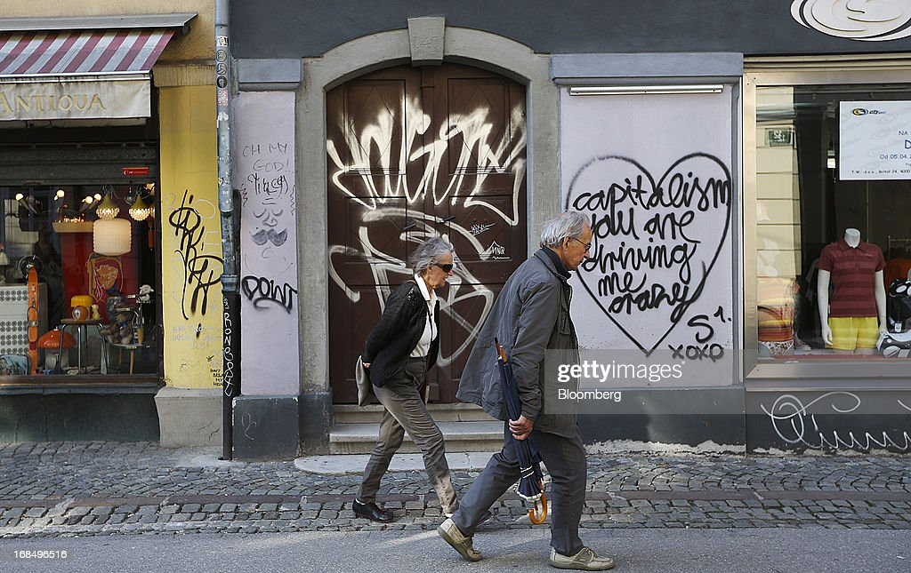 Pedestrians pass graffiti on a doorway between stores in Ljubljana, Slovenia, on Thursday, May 9, 2013. The Adriatic nation is seeking to fix its ailing lenders with a cash injection of at least 900 million euros ($1.17 billion) after Cyprus's bailout focused investors on countries with weak banking industries. Photographer: Chris Ratcliffe/Bloomberg via Getty Images