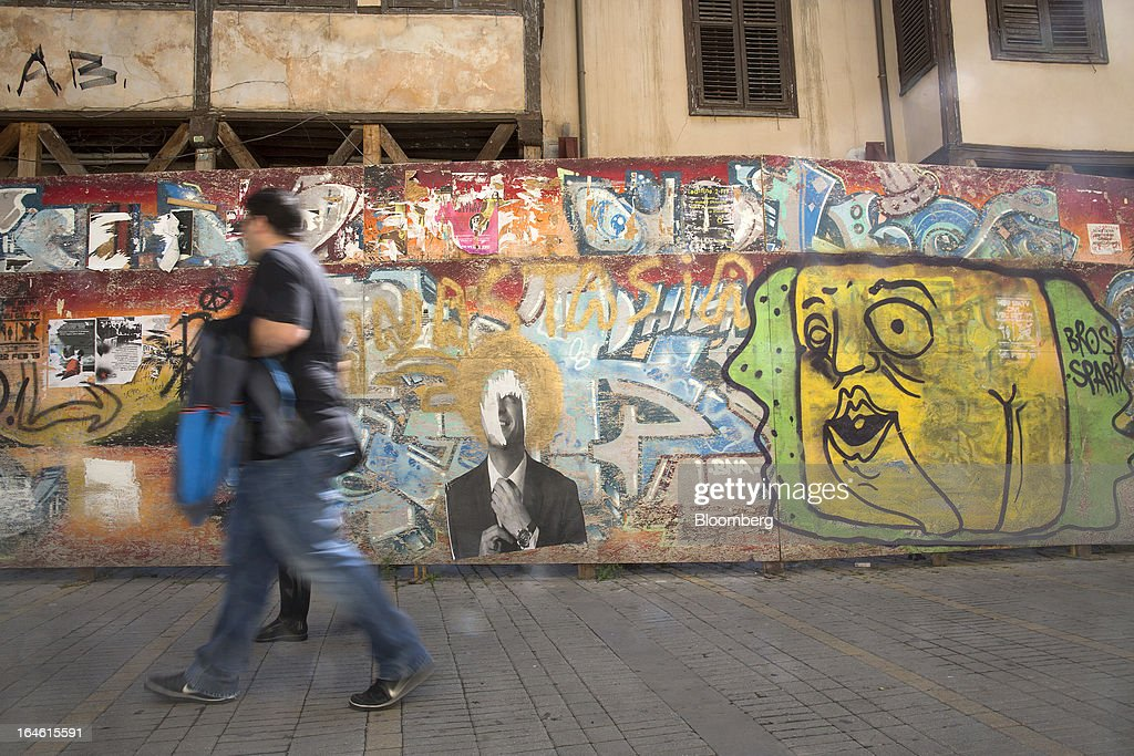 Pedestrians pass graffiti on a wall in Nicosia, Cyprus, on Monday, March 25, 2013. In a replay of tensions over aid for Greece at the outset of the crisis, European governments had wrangled over aid for Cyprus for nine months, exposing holes in the revamped economic management system that was built in three years of emergency policymaking, often at all-night summits. Photographer: Photographer: Simon Dawson/Bloomberg via Getty Images
