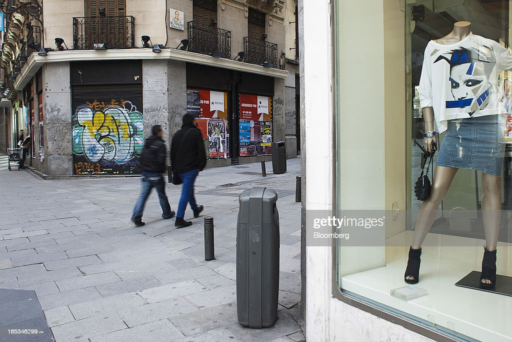 Pedestrians pass graffiti on shutters outside a closed-down retail store in Madrid, Spain, on Wednesday, April 3, 2013. Prime Minister Mariano Rajoy told Spaniards they'll start to see the benefits of his reform program next year after he avoided becoming the fifth European leader to request a full sovereign rescue. Photographer: Angel Navarrete/Bloomberg via Getty Images
