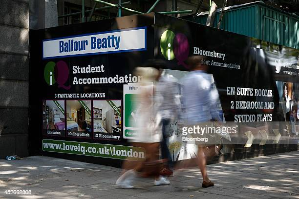 Pedestrians pass hoardings advertising student accomodation being built by Balfour Beatty Plc in the Bloomsbury district of London UK on Friday July...