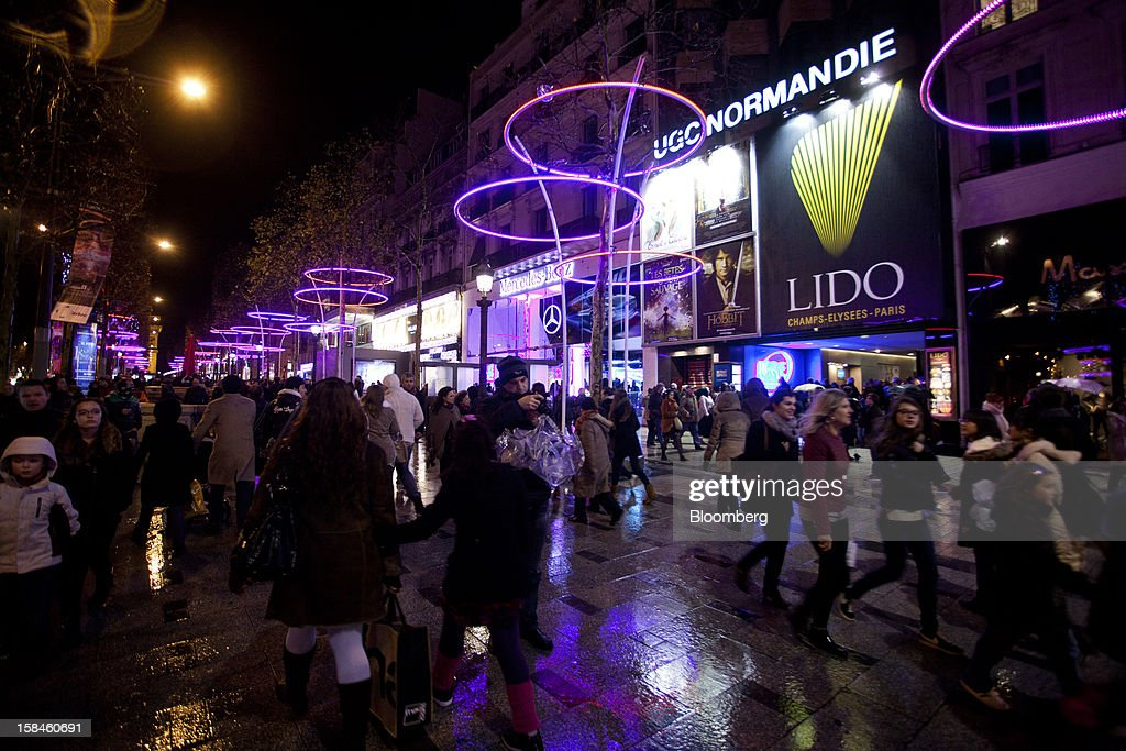 Pedestrians pass illuminated street furniture as they pass the Lido cabaret house on the Champs-Elysees in Paris, France, on Saturday, Dec. 15, 2012. The French minister for energy and environment unveiled a proposal for lights in and outside shops, offices, and public buildings -- including the flagship Louis Vuitton store and the Lido cabaret house on Paris's Avenue des Champs Elysees -- to be turned off between 1 a.m. and 7 a.m. starting in July. Photographer: Balint Porneczi/Bloomberg via Getty Images