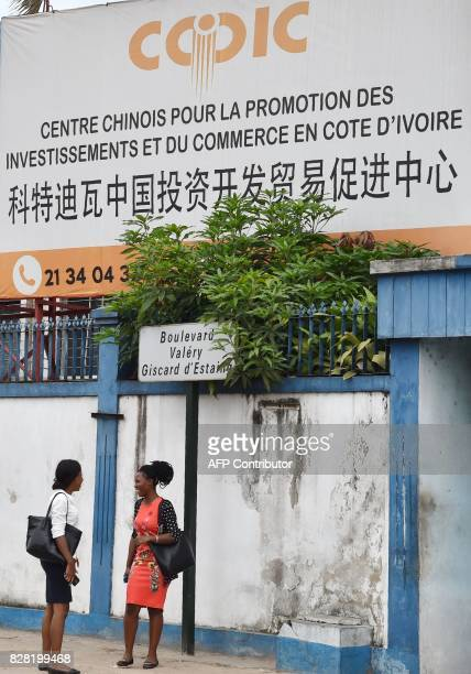 Pedestrians pass in front of a Chinese Commercial Centre in Abidjan on August 9 as China Côte d'Ivoire's third largest trading partner opened its...