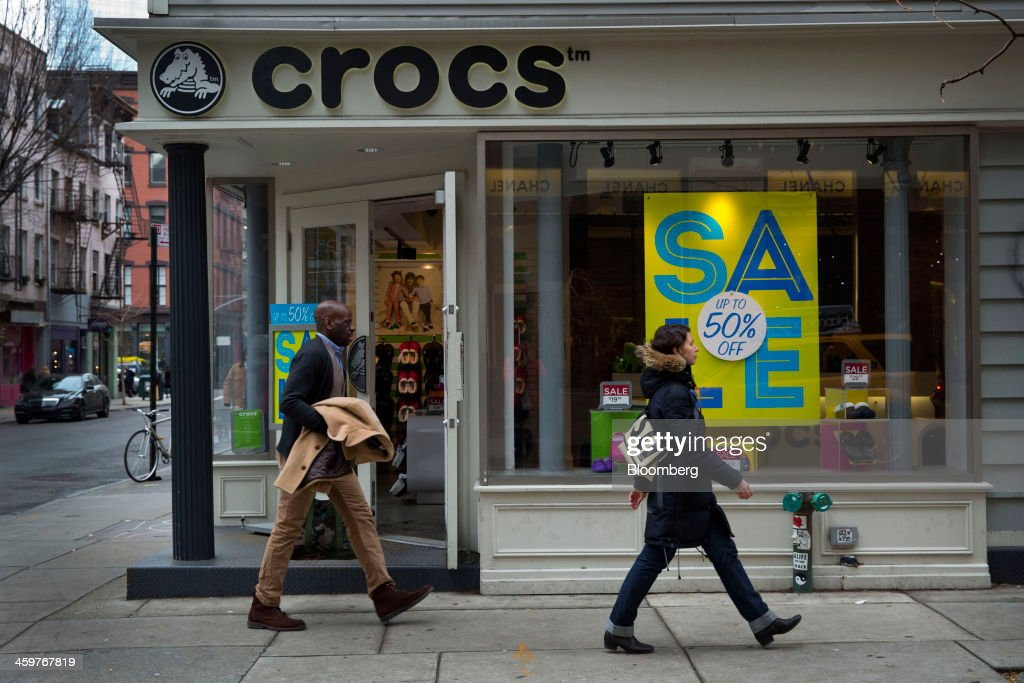 Pedestrians pass in front of a Crocs Inc. store in New York, U.S., on Monday, Dec. 30, 2013. Crocs Inc. rose as much as 14 percent in early trading after saying Chief Executive Officer John McCarvel will retire and Blackstone Group LP will invest $200 million in the maker of colorful plastic clogs. Photographer: Jin Lee/Bloomberg via Getty Images