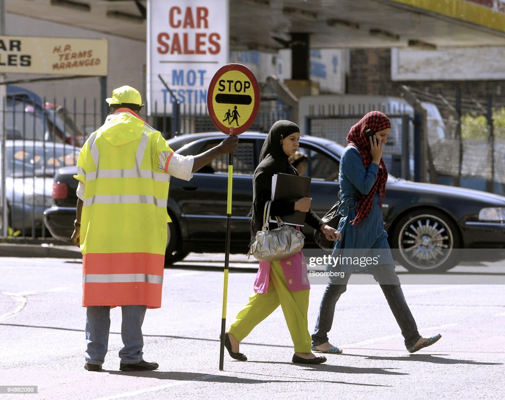 Pedestrians pass in front of a crossing guard on a street in the Alum Rock area of Birmingham UK on Monday June 9 2008 The Pakistani community is the...
