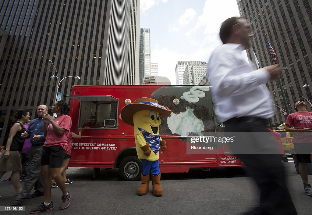 Pedestrians pass in front of a Hostess Brands LLC truck handing out Twinkies snack cakes as part of a promotion in New York, U.S., on Monday, July 15, 2013. Hostess Brands LLC officially revives sales of the iconic Twinkie snack cake today, following a seven-month hiatus after the original company decided to liquidate under bankruptcy. Photographer: Scott Eells/Bloomberg via Getty Images
