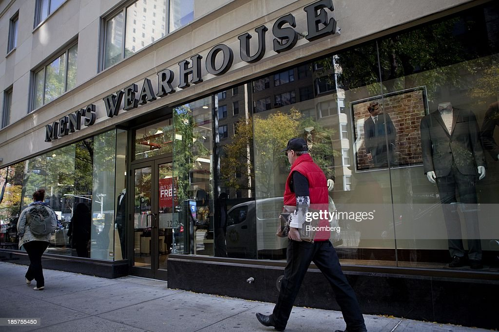 Pedestrians pass in front of a Men's Wearhouse Inc. store in New York, U.S., on Thursday, Oct. 24, 2013. Mens Wearhouse Inc., the suit retailer that rejected a $2.3 billion offer from Jos. A. Bank Clothiers Inc., may bid for Allen Edmonds Corp., a closely held shoemaker, according to a person familiar with the matter. Photographer: Mati Milstein/Bloomberg via Getty Images