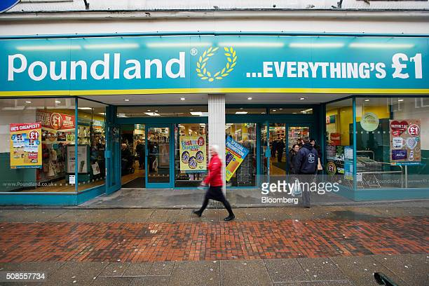 Pedestrians pass in front of a Poundland Group Plc store in Leigh UK on Thursday Feb 4 2016 UK like for like sales at midmarket retailers rose 14...