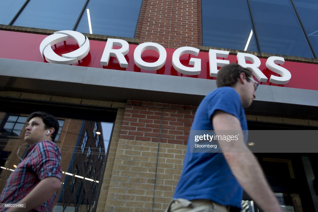 Pedestrians pass in front of a Rogers Communications Inc. store in Toronto, Ontario, Canada, on Wednesday, May 17, 2017. Rogers Communications, Canada's largest wireless carrier, is leveraging organic growth in the country's wireless market to expand its subscriber base. Photographer: Brent Lewin/Bloomberg via Getty Images