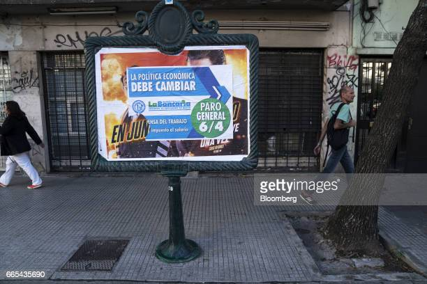 Pedestrians pass in front of a sign that reads 'The Economic Policy Must Change General Strike April 6' in Buenos Aires Argentina on April 6 2017...