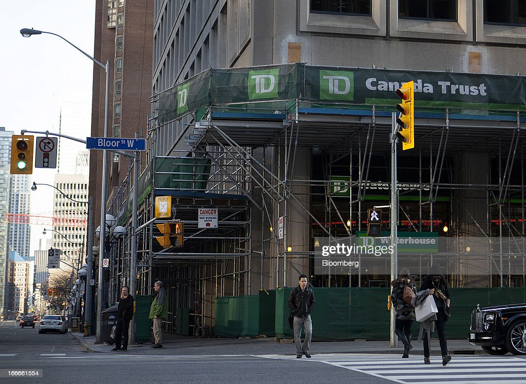 Pedestrians pass in front of a Toronto-Dominion Bank branch surrounded by scaffolding in Toronto, Ontario, Canada, on Sunday, April 14, 2013. The Canadian dollar fluctuated against its U.S. counterpart amid speculation the economy is slowing after an unexpected jobs loss last month. Photographer: Pawel Dwulit/Bloomberg via Getty Images