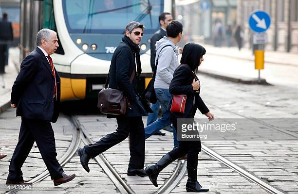 Pedestrians pass in front of a tram as they cross Cordusio square in Milan Italy on Friday March 16 2012 Prime Minister Mario Monti's planned...