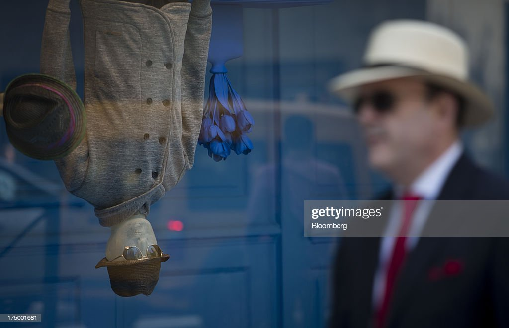 Pedestrians pass in front of a window display at Saks Fifth Avenue in New York, U.S., on Monday, July 29, 2013. Hudson's Bay Co. agreed to buy Saks Inc. for $2.4 billion, combining Canada's largest-department store chain with one of the most prestigious U.S. luxury retailers in a deal that may spur the creation of a real estate investment trust. Photographer: Scott Eells/Bloomberg via Getty Images