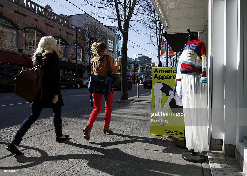 Pedestrians pass in front of an American Apparel Inc. store on Robson St. in Vancouver, British Columbia, Canada, on Monday, March 25, 2013. Statistics Canada (STCA) is scheduled to release consumer price index data on March 27, 2013. Photographer: Ben Nelms/Bloomberg via Getty Images