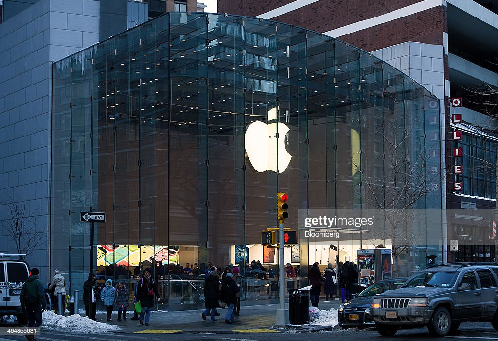 Pedestrians pass in front of an Apple Inc. store in New York, U.S., on Thursday, Jan. 23, 2014. Billionaire investor Carl Icahn said he increased his stake in Apple Inc. by another $500 million, bringing his total holdings in the iPhone maker to about $3.6 billion as he reiterated calls for a bigger stock buyback. Photographer: Ron Antonelli/Bloomberg via Getty Images