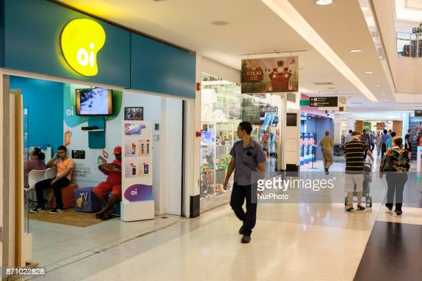 Pedestrians pass in front of an Oi SA store in a shopping mall in the city of Recife in the Northeast of Brazil on November 6 2017 Recently Oi SA...