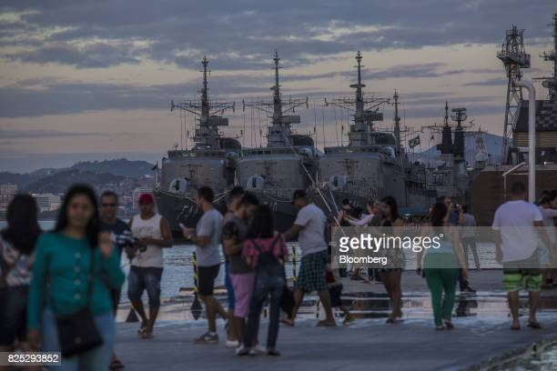 Pedestrians pass in front of navy ships docked outside a military facility in downtown Rio de Janeiro Brazil on Sunday July 30 2017 Thousands of...