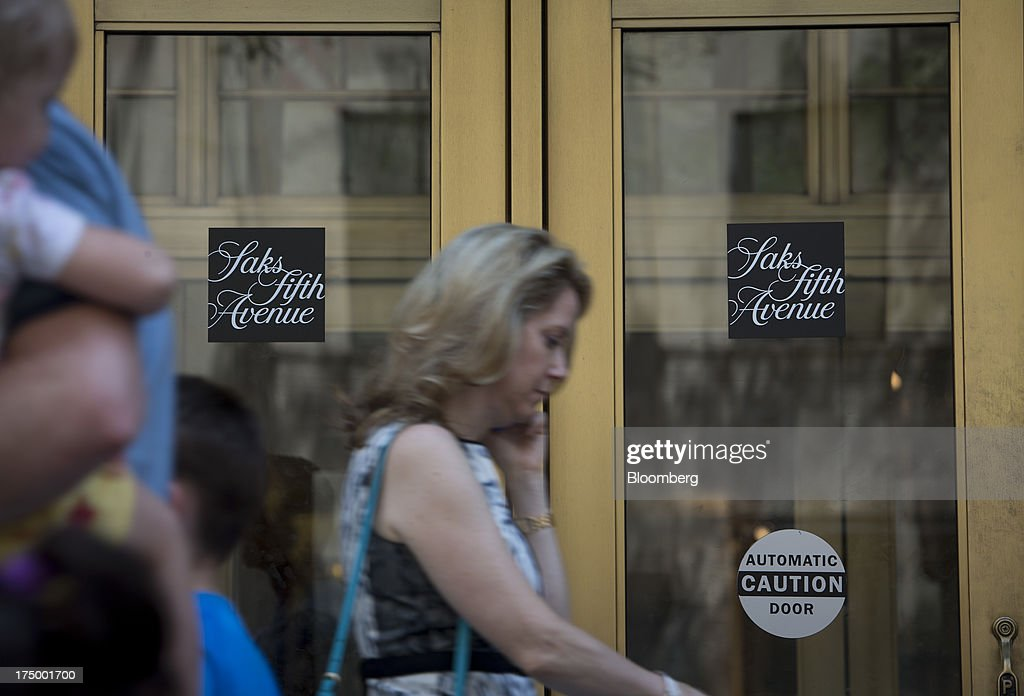 Pedestrians pass in front of Saks Fifth Avenue in New York, U.S., on Monday, July 29, 2013. Hudson's Bay Co. agreed to buy Saks Inc. for $2.4 billion, combining Canada's largest-department store chain with one of the most prestigious U.S. luxury retailers in a deal that may spur the creation of a real estate investment trust. Photographer: Scott Eells/Bloomberg via Getty Images