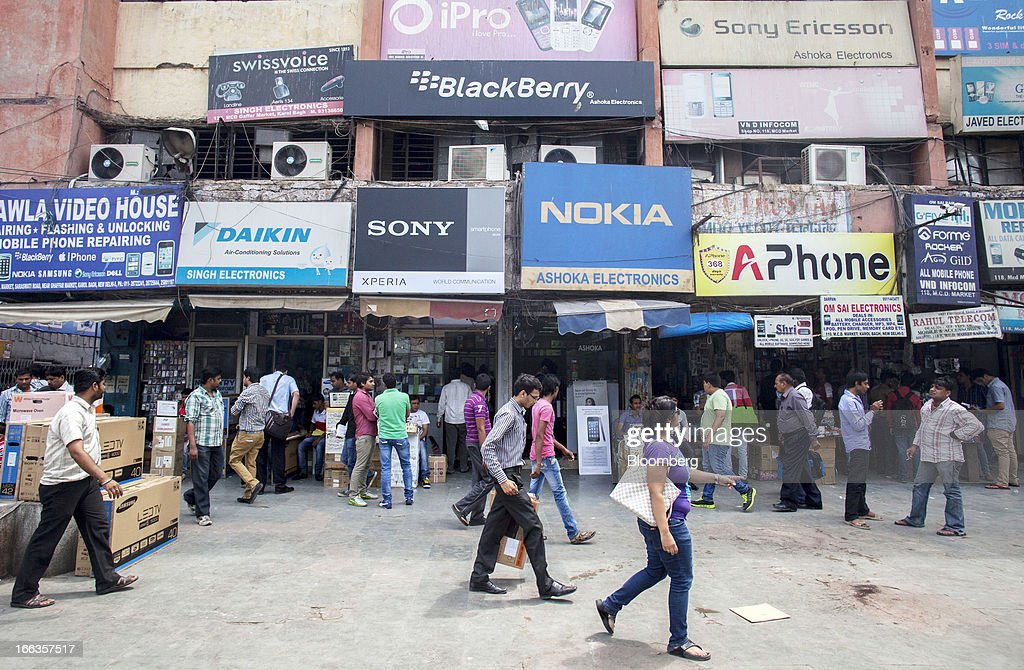 Pedestrians pass in front of smartphone wholesale outlets at Gaffar Market in New Delhi, India, on Tuesday, April 9, 2013. Apple Inc. and Samsung Electronics Co. are being outpaced in the fast-growing Indian smartphone market by aggressive local competitors Micromax Informatics Ltd. and Karbonn Mobiles India Pvt. Ltd. Photographer: Prashanth Vishwanathan/Bloomberg via Getty Images
